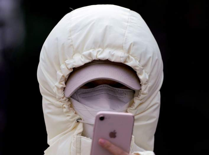 A woman wearing a mask checks her mobile phone in Shanghai, China January 29, 2020. REUTERS/Aly Song