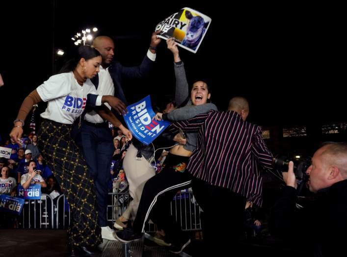 Anti-dairy industry protestors are pulled from the stage as Democratic U.S. presidential candidate and former Vice President Joe Biden speaks at his Super Tuesday night rally in Los Angeles, California, U.S., March 3, 2020. REUTERS/Kyle Grillot