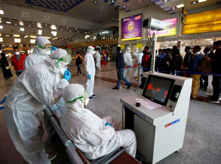 Medical staff in protective gear look at a screen while checking temperatures of passengers upon their arrival, following an outbreak of the coronavirus, at Najaf airport, in the holy city of Najaf, Iraq February 26, 2020. Picture taken February 26, 2020.