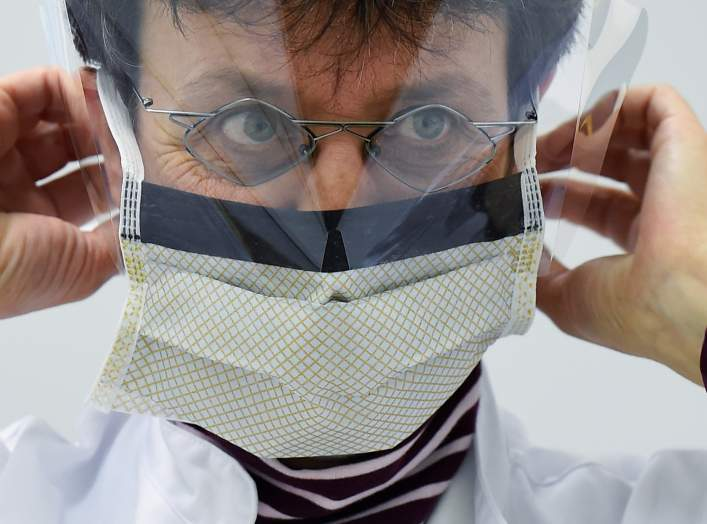 Chief doctor Katja de With puts on a protection mask during a media event in the newly opened coronavirus disease (COVID-19) clearing-up centre in Dresden, Germany, March 9, 2020. REUTERS/Matthias Rietschel