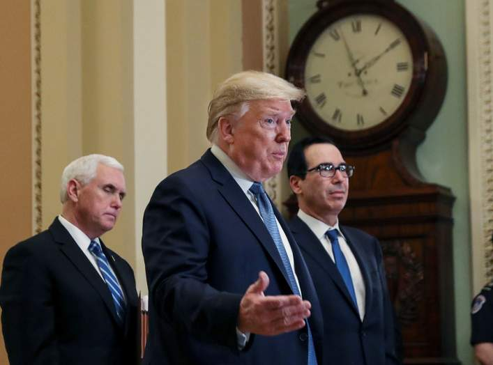 U.S. President Donald Trump is flanked by Vice President Mike Pence and Treasury Secretary Steven Mnuchin as he speaks to members of the news media following a closed Senate Republican policy lunch meeting to discuss the response to the coronavirus outbre