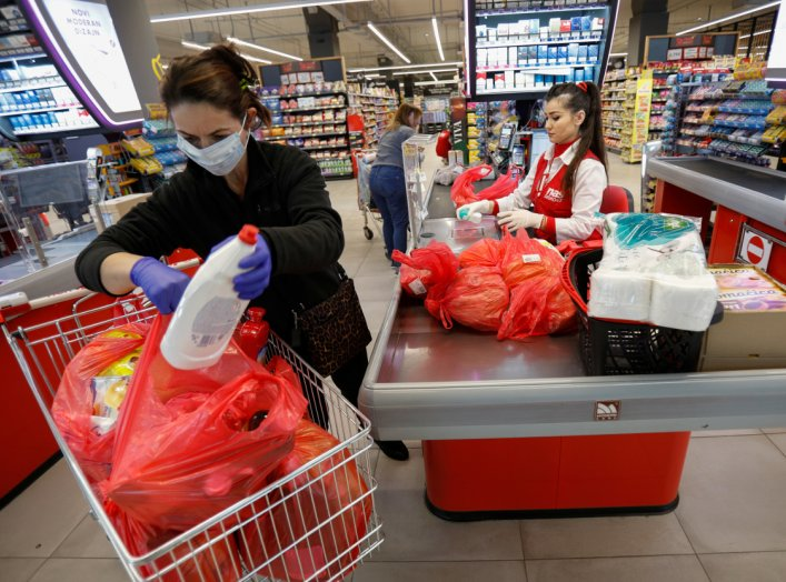A women wearing a mask packs her groceries after the government limited the number of customers in supermarkets to 50 at a time due to coronavirus (COVID-19) threat in Podgorica, Montenegro March 16, 2020. REUTERS/Stevo Vasiljevic