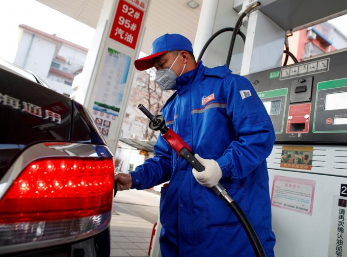 A pump attendant wears a mask as he refuels a car at a Sinopec gas station where customers can buy supplies as the country is hit by an outbreak of the novel coronavirus, in Beijing, China, February 28, 2020. REUTERS/Thomas Peter