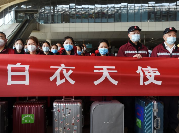 Medical workers from outside Wuhan stand behind a banner with their suitcases as they listen to a speech at the Wuhan Railway Station before leaving the epicentre of the novel coronavirus disease (COVID-19) outbreak, in Hubei province, China