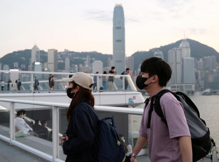 People with protective masks walk in front of Hong Kong's skyline, following the novel coronavirus disease (COVID-19) outbreak, China March 23, 2020. REUTERS/Tyrone Siu