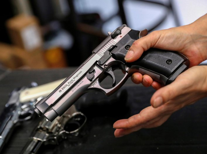 A Hungarian vendor shows an Ekol Firat Magnum gas pistol at a gun shop where people queued up to buy weapons for protection during the coronavirus pandemic, in Budapest, March 20, 2020. REUTERS/Bernadett Szabo