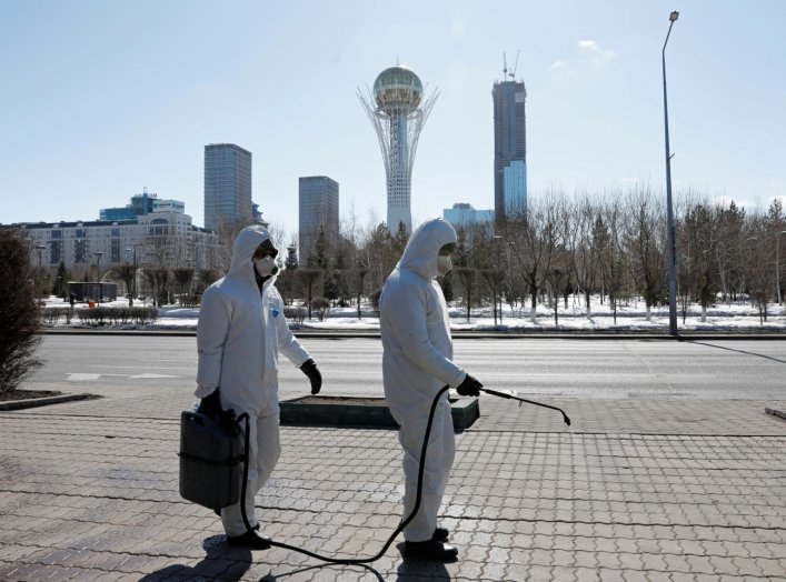 Workers wearing protective suits spray disinfectant on the street to prevent the spread of coronavirus disease (COVID-19), in central Nur-Sultan, Kazakhstan March 24, 2020. REUTERS/Mukhtar Kholdorbekov