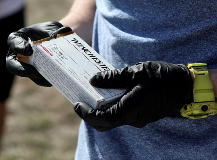 Firearms instructor Joseph Wilkey wears gloves while holding a box of 9mm Winchester ammunition during a firearms safety class conducted by Level Up Firearms amid fears of the global growth of coronavirus disease (COVID-19) cases, outside Loveland, Colora