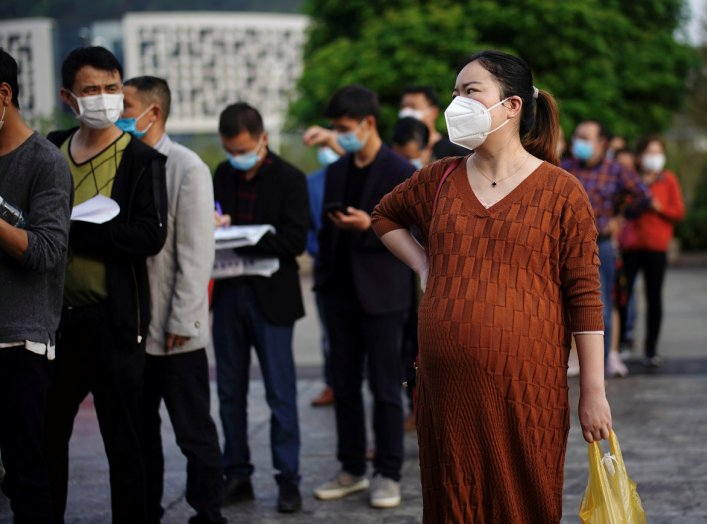 People wearing face masks line up outside Xianning Central Hospital in Xianning, after the lockdown was eased in Hubei province, the epicentre of China's coronavirus disease (COVID-19) outbreak, March 26, 2020. REUTERS/Aly Song