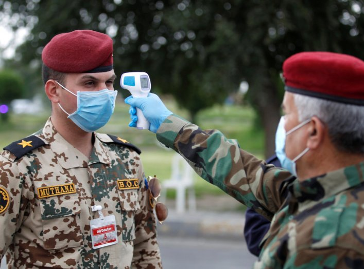 An Iraqi soldier wears a protective face mask and gloves as he checks the temperature of an Iraqi officer, during a curfew imposed to prevent the spread of the coronavirus disease (COVID-19), in Baghdad, Iraq March 27, 2020. REUTERS/Khalid al-Mousily