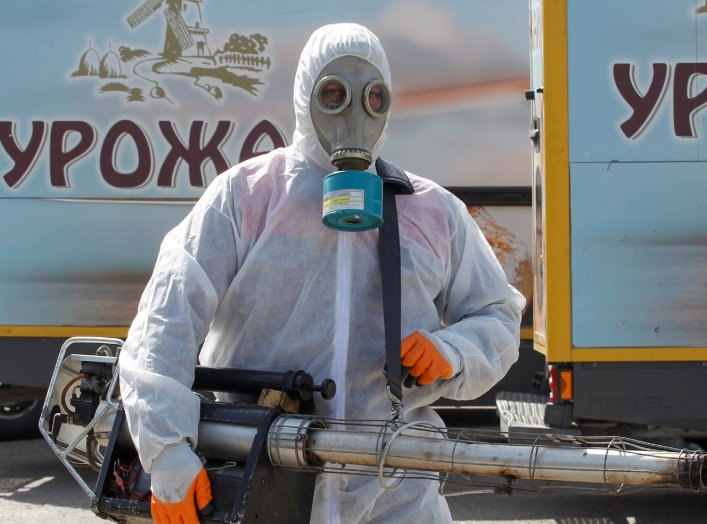 "A specialist with protective gear sanitizes the facilities of a local bakery to prevent the spread of coronavirus disease (COVID-19) in the rebel-controlled city of Donetsk, Ukraine March 27, 2020. The logos on the trucks read ""Harvest"". REUTERS/Alexander"