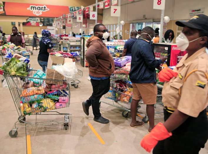 People queue to pay for goods at a supermarket ahead of a nationwide 21-day lockdown called by the government to limit the spread of coronavirus disease (COVID-19) in Harare, Zimbabwe, March 28, 2020. REUTERS/Philimon Bulawayo