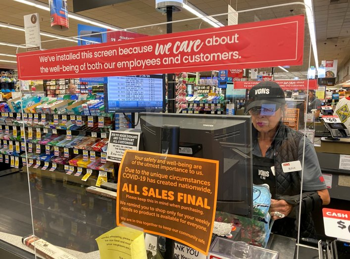 A grocery store worker is protected by a shield at a Vons store during the outbreak of the coronavirus disease (COVID-19) in Solana Beach, California, U.S., March 29, 2020. REUTERS/Mike Blake