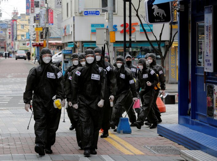 South Korean soldiers in protective gear make their way while they disinfect buildings downtown, following the rise in confirmed cases of coronavirus disease (COVID-19) in Daegu, South Korea, March 15, 2020. REUTERS/Kim Kyung-Hoon