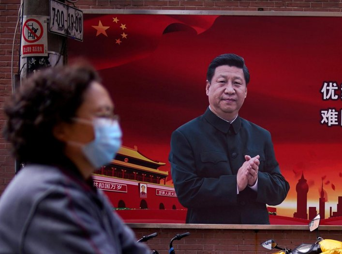 A woman wearing a protective mask is seen past a portrait of Chinese President Xi Jinping on a street as the country is hit by an outbreak of the coronavirus, in Shanghai, China March 12, 2020. REUTERS/Aly Song