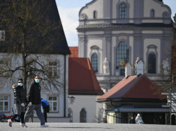Two persons walk on an empty square at the Graciousness Chapel in Altoetting, Germany, March 31, 2020 as the spread of the coronavirus disease (COVID-19) continues. REUTERS/Andreas Gebert