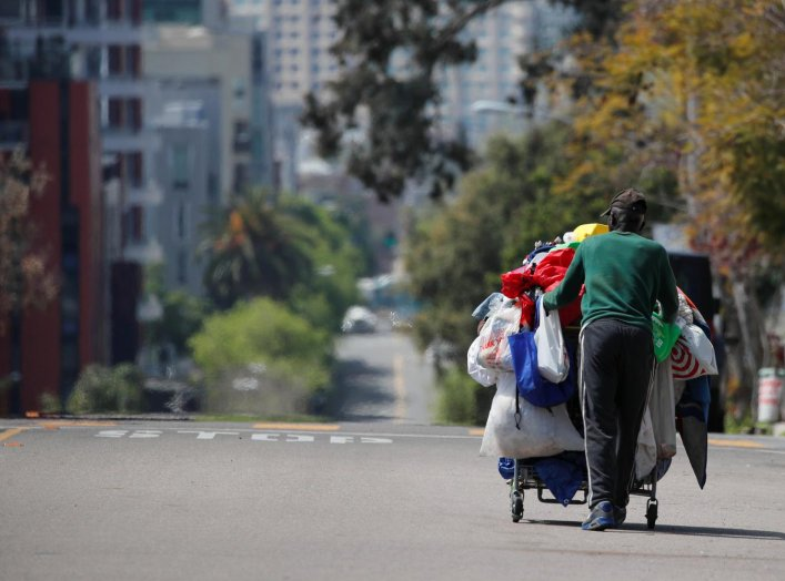 A homeless man pushes a cart full of his belongings along an empty street during the outbreak of the coronavirus disease (COVID-19) in San Diego, California, U.S., April 1, 2020. REUTERS/Mike Blake