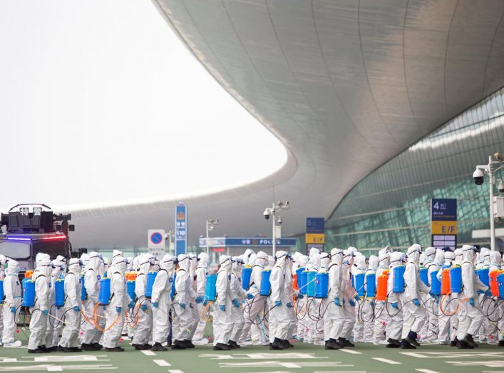 Firefighters in protective suits are seen during an operation to disinfect Wuhan Tianhe International Airport before the airport resumes its domestic flights on April 8, in Wuhan, Hubei province, the epicentre of China's novel coronavirus disease (COVID-1