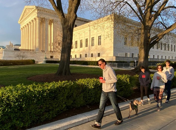 A family walk their dog past the U.S. Supreme Court building at sunset during the outbreak of the coronavirus disease (COVID-19), as personal exercise is exempted from the city-wide stay at home orders in Washington, U.S. April 3, 2020. REUTERS/Jonathan E
