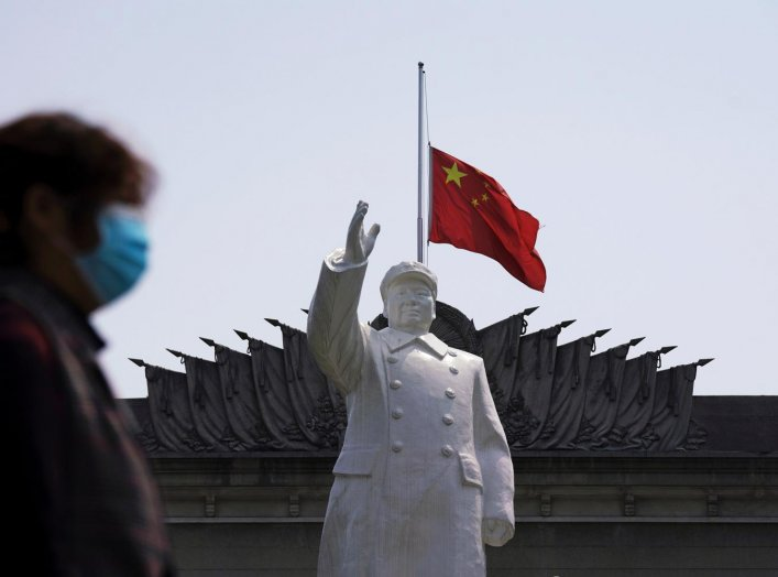 The Chinese national flag flies at half-mast behind a statue of late Chinese chairman Mao Zedong in Wuhan, Hubei province, as China holds a national mourning for those who died of the coronavirus disease (COVID-19), on the Qingming tomb-sweeping festival,