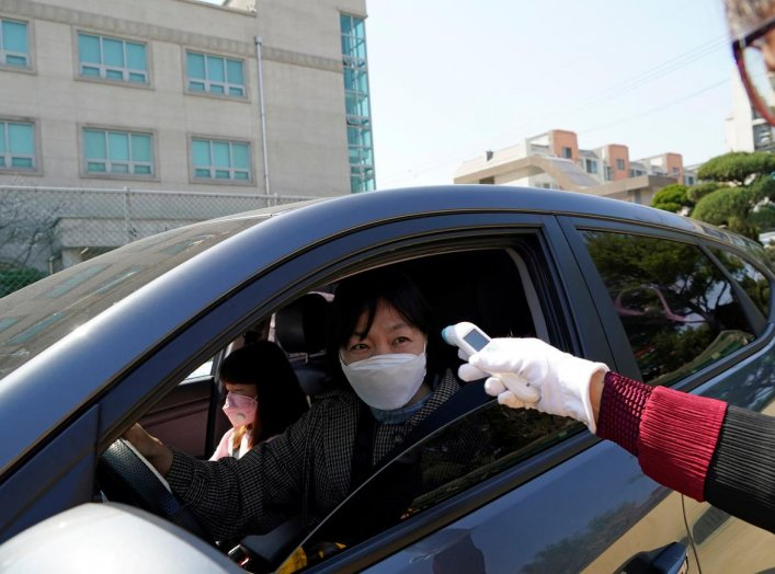 A South Korean Christian wearing a protective face mask has her temperature checked while attending a drive-in worship service following the outbreak of the coronavirus disease (COVID-19) in Seoul, South Korea, April 5, 2020. REUTERS/Kim Hong-Ji