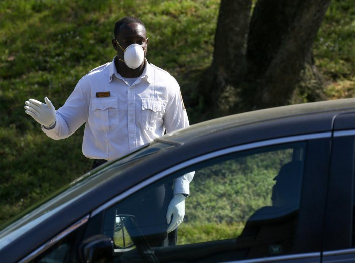 A first responder greets patients waiting in their cars to enter the Covid-19 testing center at UMC Hospital, the sole hospital in Washington's Ward 8, which has the city's highest poverty rate according to census data, during the coronavirus outbreak in
