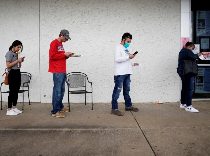 People who lost their jobs wait in line to file for unemployment following an outbreak of the coronavirus disease (COVID-19), at an Arkansas Workforce Center in Fayetteville, Arkansas, U.S. April 6, 2020. REUTERS/Nick Oxford