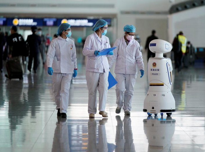 Medical workers walk by a police robot at the Wuhan Tianhe International Airport after travel restrictions to leave Wuhan, the capital of Hubei province and China's epicentre of the novel coronavirus disease (COVID-19) outbreak, were lifted, April 8, 2020