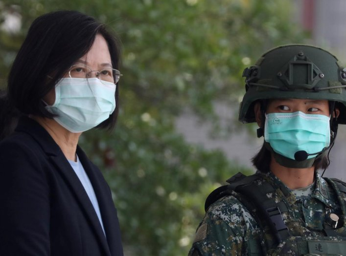 Taiwanese president Tsai Ing-Wen, wearing a mask, observe soldiers demonstrate drills at a military base camp in Tainan, Taiwan, April 9, 2020. REUTERS/Ann Wang