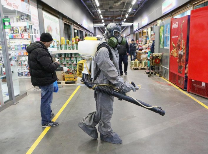 A specialist wearing protective gear sprays disinfectant inside the FOOD CITY wholesale and retail market to prevent the spread of the coronavirus disease (COVID-19) in Moscow, Russia April 9, 2020. Andrey Nikerichev/Moscow News Agency/Handout via REUTERS