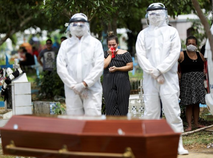 Relatives of 68-years-old Natalina Cardoso Bandeira, who passed away due to coronavirus disease (COVID-19), react during her burial at the Parque Taruma cemetery in Manaus, Brazil, April 10, 2020. REUTERS/Bruno Kelly