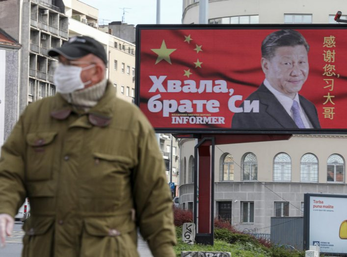 """A man wearing a protective mask passes by a billboard depicting Chinese President Xi Jinping as the spread of the coronavirus disease (COVID-19) continues in Belgrade, Serbia, April 1, 2020. The text on the billboard reads """"Thanks, brother Xi"""". Picture ta"""