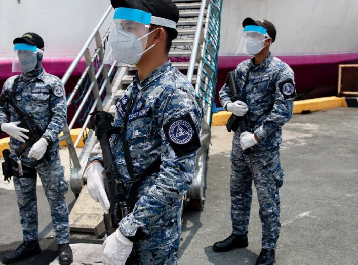 Members of the Philippine Coast Guard wearing protective masks hold their weapons with gloves outside a passenger vessel turned into a temporary quarantine facility for Filipino seafarers to contain the coronavirus disease (COVID-19) in Manila, Philippine