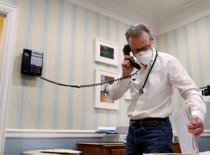 Dr Greg Gulbransen takes part in a telemedicine call with a patient while maintaining visits with both his regular patients and those confirmed to have the coronavirus disease (COVID-19) at his pediatric practice in Oyster Bay, New York, U.S., April 13, 2