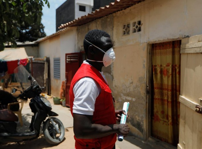 Cheikhou Dembele, 25, Senegalese Red Cross volunteer, waits outside a house during an awareness campaign to prevent the spread of coronavirus disease (COVID-19), in Dakar, Senegal April 18, 2020. REUTERS/Zohra Bensemra