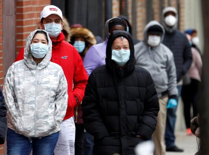 People wearing protective face masks wait in line outside NYC Health + Hospitals/Gotham Health Morrisania neighborhood health center, one of New York City's new walk-in COVID-19 testing centers, during the outbreak of the coronavirus disease (COVID-19) in