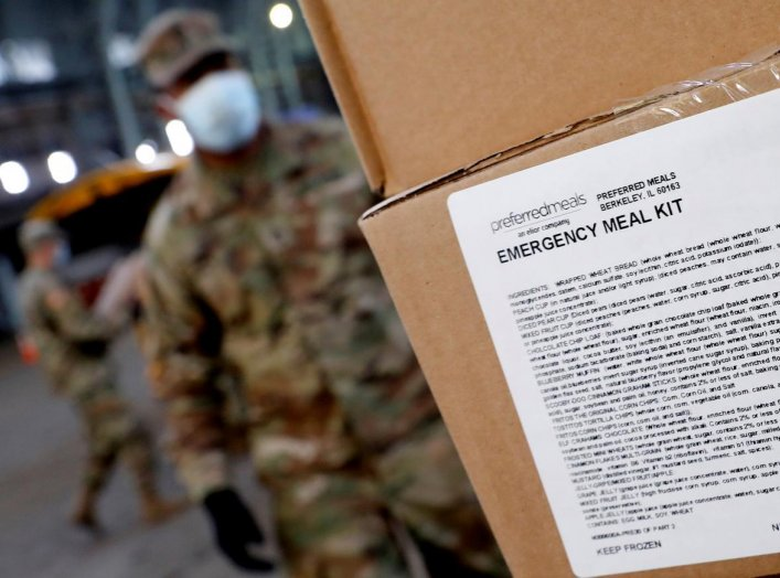 A U.S. Army National Guard soldier wears a protective face mask while loading a vehicle with food for delivery to residents in need at the Kingsbridge Armory which is being used as a temporary food distribution center during the outbreak of the coronaviru