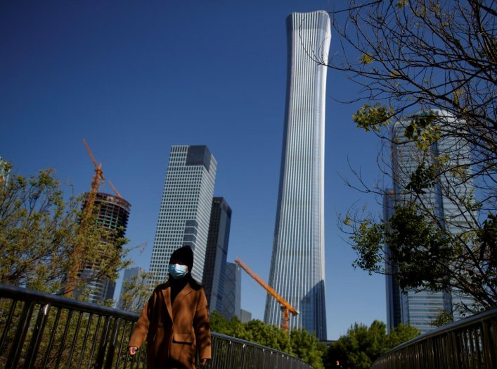 """A woman wearing a protective mask walks near the Central Business District on a """"blue sky day"""" in Beijing as the spread of the novel coronavirus disease (COVID-19) continues, in China April 22, 2020. REUTERS/Thomas Peter"""
