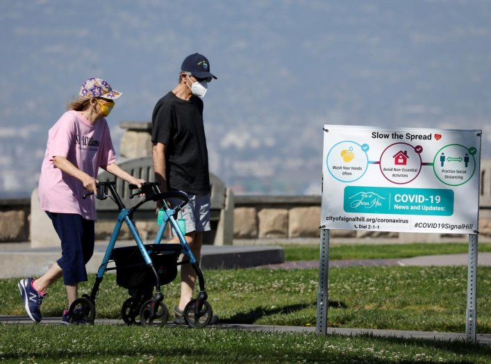 An elderly couple wear masks as they get some exercise in a park during the outbreak of the coronavirus disease (COVID-19) in Signal Hill, California, U.S., April 23, 2020. REUTERS/Mike Blake