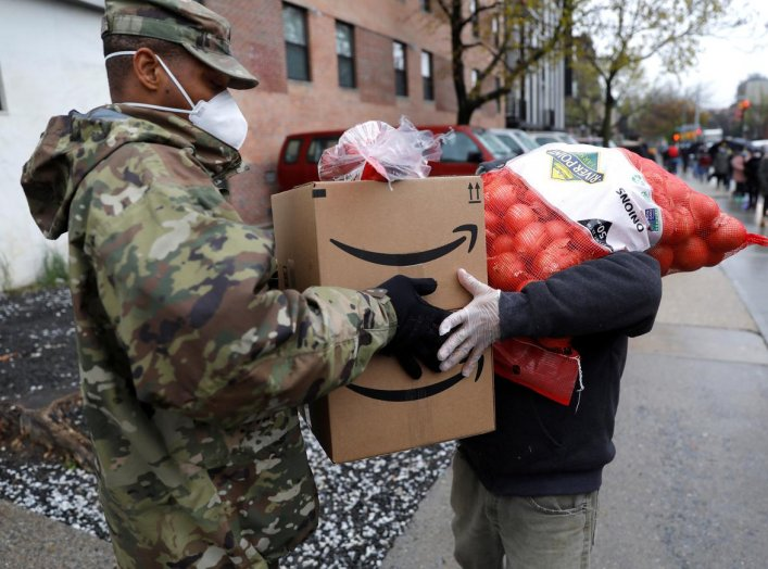 A U.S. Army National Guard soldier gives food to a man at a curbside food pantry for needy residents during the outbreak of the coronavirus disease (COVID-19) in the Brooklyn borough of New York City, New York, U.S., April 24, 2020. REUTERS/Mike Segar