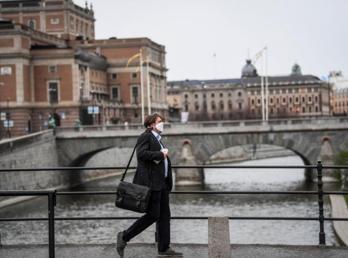 A man wearing a protective mask walks past the Royal Swedish Opera, amid the coronavirus disease (COVID-19) outbreak in Stockholm, Sweden, April 27, 2020. Fredrik Sandberg/TT News Agency/via REUTERS