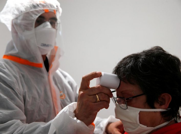 A French doctor wearing a protective suit checks the temperature of a woman in a testing site for the coronavirus disease (COVID-19) in Gouzeaucourt, France, April 28, 2020. REUTERS/Pascal Rossignol