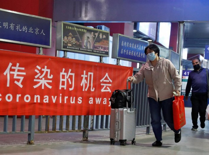 People wearing protective face masks walks by a regional bus station in Beijing as the spread of the coronavirus disease (COVID-19) continues in Beijing, China April 30, 2020. REUTERS/Thomas Peter