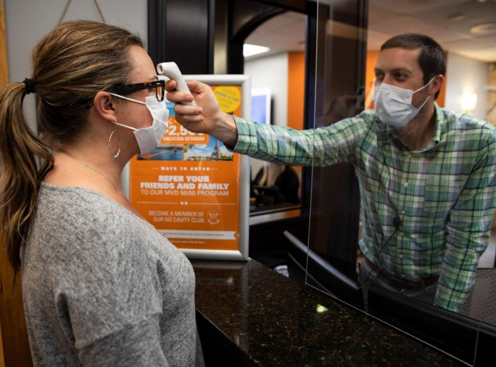 A dentist office manager takes the temperature of a woman as Ohio implements phase one of reopening dentists, veterinarians and elective surgeries, following the outbreak of the coronavirus disease (COVID-19), in Columbus, Ohio, U.S., May 01, 2020. REUTER