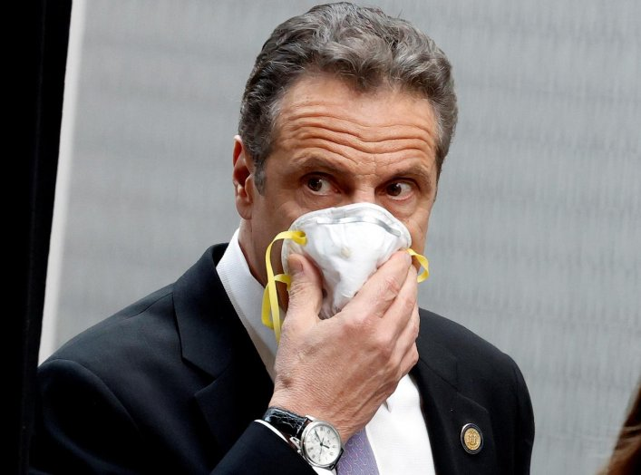 New York Governor Andrew Cuomo holds a protective mask to his face as he arrives for a daily briefing at New York Medical College during the outbreak of the coronavirus disease (COVID-19) in Valhalla, New York, U.S., May 7, 2020. REUTERS/Mike Segar
