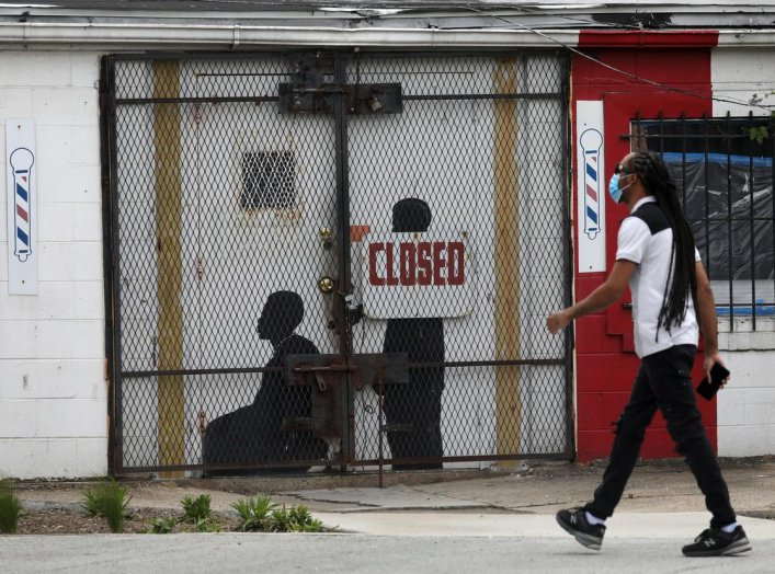 A pedestrian walks past a closed barber shop in Ward 7 as the coronavirus disease (COVID-19) outbreak continues in Washington, U.S., May 8, 2020. REUTERS/Leah Millis