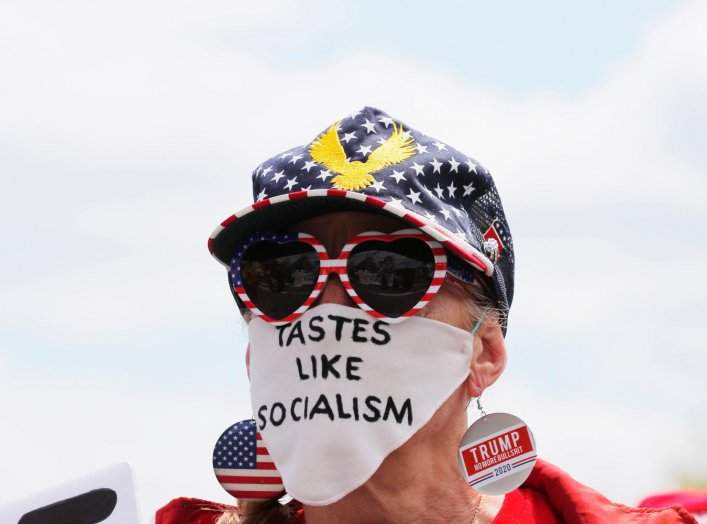 """A woman wears a mask reading """"Tastes Like Socialism"""" at a protest against restrictions implemented in response to the coronavirus disease (COVID-19) outbreak near Massachusetts Governor Charlie Baker's house in Swampscott, Massachusetts, U.S., May 16, 202"""