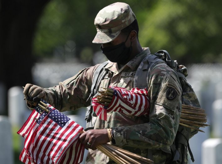 A U.S. Army Old Guard member holds small American flags to put in front of the headstones of U.S. service members buried at Arlington National Cemetery in Arlington, Virginia, U.S., May 21, 2020. REUTERS/Tom Brenner