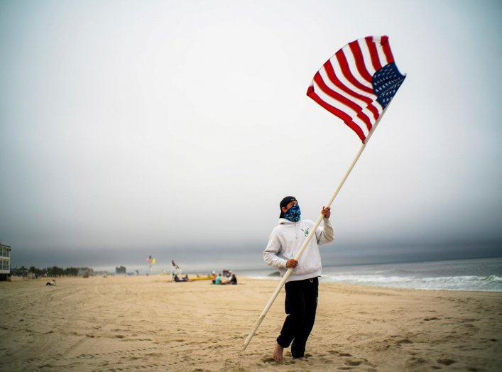 A beach guard removes the U.S. flag of his spot after a day of duty at Long Branch beach after New Jersey beaches were opened ahead of the Memorial Day weekend following the outbreak of the coronavirus disease (COVID-19) in Long Branch, New Jersey, U.S.,