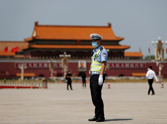 A police officer wearing a face mask following the coronavirus disease (COVID-19) outbreak stands on Tiananmen Square before the closing session of the National People's Congress (NPC) in Beijing, China May 28, 2020. REUTERS/Carlos Garcia Rawlins